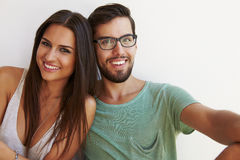 Portrait Of Couple Sitting Against White Wall Stock Photos