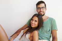 Portrait Of Couple Sitting Against White Wall Stock Image
