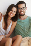 Portrait Of Couple Sitting Against White Wall Stock Photography