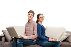 Portrait of couple sitting back to back on couch with laptops. Isolated portrait of couple sitting back to back on couch with laptops Stock Photo