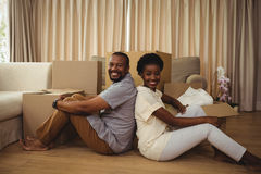 Portrait of couple sitting back to back in living room. Portrait of happy couple sitting back to back in living room at home Stock Photography