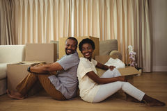 Portrait of couple sitting back to back in living room. Portrait of happy couple sitting back to back in living room at home Royalty Free Stock Photo