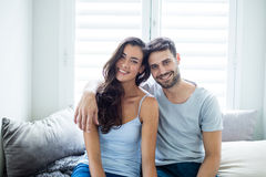 Portrait of couple sitting on bed in bedroom Stock Images