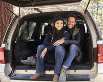 Portrait of couple sitting in open back of car before hiking Stock Photo