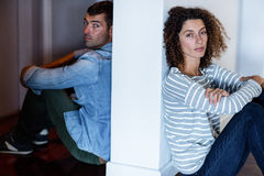 Portrait of couple sitting on opposite sides of the wall Royalty Free Stock Photography