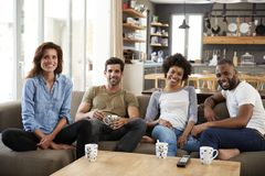 Portrait Of Couple Sitting On Sofa With Friends At Home Talking Royalty Free Stock Images