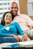 Portrait Of Couple Sitting On Sofa Together Stock Photography