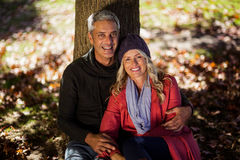 Portrait of couple sitting under tree Royalty Free Stock Images