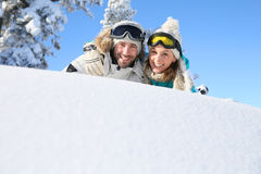 Portrait of a couple of skiers lying in the snow Royalty Free Stock Images