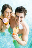 Portrait of a couple smiling and drinking a cocktail in a pool Stock Photos