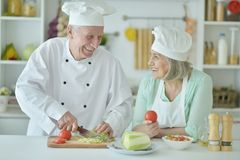 Portrait of couple of smiling senior chefs at kitchen. Couple of smiling senior chefs posing at kitchen at home royalty free stock images