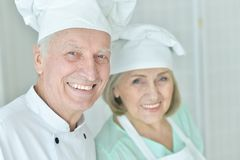 Portrait of couple of smiling senior chefs at kitchen. Couple of smiling senior chefs posing at kitchen at home stock photos