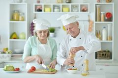 Portrait of couple of smiling senior chefs at kitchen. Couple of smiling senior chefs posing at kitchen at home stock photography