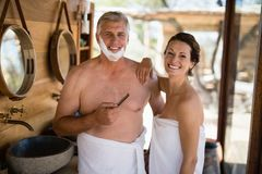 Portrait of couple smiling while shaving in cottage Stock Photos