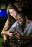 Portrait of couple smiling and toasting their wine glasses at bar counter. In bar Stock Photography