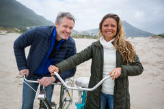 Portrait of couple standing with bicycle on beach Stock Photo