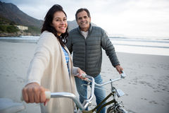Portrait of couple standing with bicycle on beach Stock Image