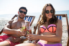 Portrait of couple toasting drinks while relaxing on deck chairs at beach Royalty Free Stock Images