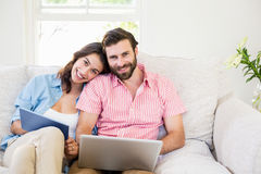 Portrait of couple using digital tablet and laptop Stock Images