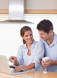 Portrait of a couple using a laptop while having tea Stock Photo