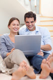 Portrait of a couple using a laptop while lying on a sofa Royalty Free Stock Images