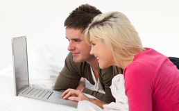 Portrait of a couple using a latop in bed Royalty Free Stock Photo