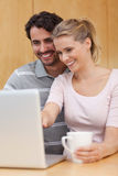 Portrait of a couple using a notebook while having tea Royalty Free Stock Photography