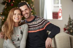 Portrait Of Couple Wearing Festive Jumpers Sitting On Sofa In Lounge At Home On Christmas Day royalty free stock photos