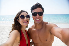 Portrait of couple wearing sunglasses at beach Stock Image