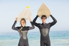 Portrait of couple in wetsuit carrying surfboard over head Stock Image