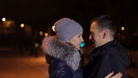 Portrait of couple in winter in the park at night. A loving couple is standing in an embrace in the winter evening in the park. Portrait of a couple in winter stock video