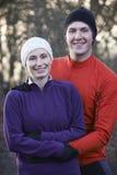 Portrait Of Couple On Winter Run Through Woodland Stock Image