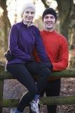 Portrait Of Couple On Winter Run Through Woodland Sitting On Fen Stock Image