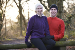 Portrait Of Couple On Winter Run Through Woodland Sitting On Fen Royalty Free Stock Photo