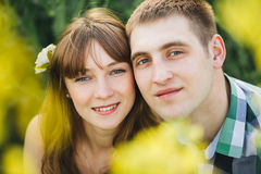 Portrait of couple of young boyfriend and girlfriend smiling at camera. Couple among flowers, touching by face each other. Brunett Stock Image