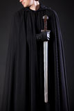 Portrait of a courageous warrior wanderer in a black cloak and sword in hand. Portrait of a courageous warrior wanderer in a black cloak and sword Royalty Free Stock Photo