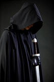 Portrait of a courageous warrior wanderer in a black cloak and sword in hand. Portrait of a courageous warrior wanderer in a black cloak and sword Royalty Free Stock Image