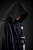 Portrait of a courageous warrior wanderer in a black cloak and sword in hand. Stock Photos
