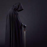 Portrait of a courageous warrior wanderer in a black cloak and sword in hand. Portrait of a courageous warrior wanderer in a black cloak and sword Royalty Free Stock Photos