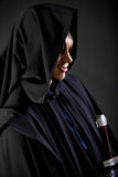 Portrait of a courageous warrior wanderer in a black cloak and sword in hand. Portrait of a courageous warrior wanderer in a black cloak and sword Royalty Free Stock Photography