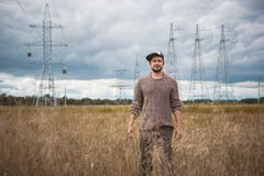 Portrait of courageous young man in cap on meadow, energy pylons at background. Cloudy autumn Royalty Free Stock Image