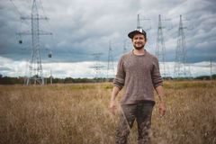 Portrait of courageous young man in cap on meadow, energy pylons at background, wide angle Royalty Free Stock Image