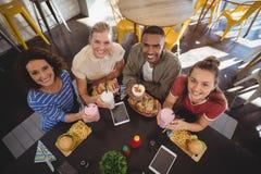 Portrait courbe de jeunes amis de sourire s'asseyant avec le déjeuner au café Photo libre de droits