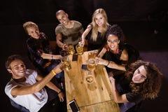 Portrait courbe des amis heureux grillant à la table Images stock
