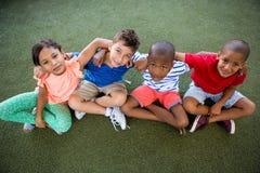 Portrait courbe des enfants heureux s'asseyant sur l'herbe Images libres de droits