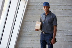 Portrait Of Courier Collecting Package From Office Royalty Free Stock Photo