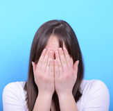 Portrait of covering her face with hands against blue background Royalty Free Stock Image