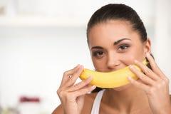 Portrait créatif de femme tenant la banane jaune dans sa main Photos stock
