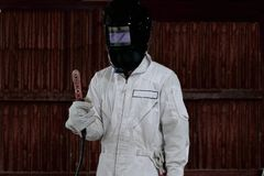 Portrait of craftsman welder in white uniform holding arc welding torch in hands. Industrial worker concept. Stock Image