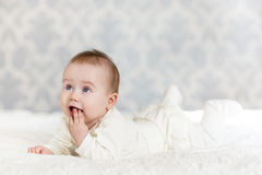 Portrait of a crawling baby on the bed in her room Stock Photo
